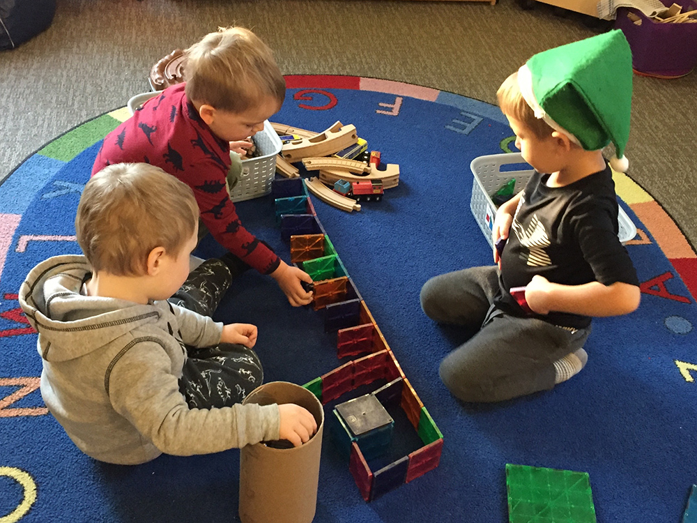 Three boys playing with blocks
