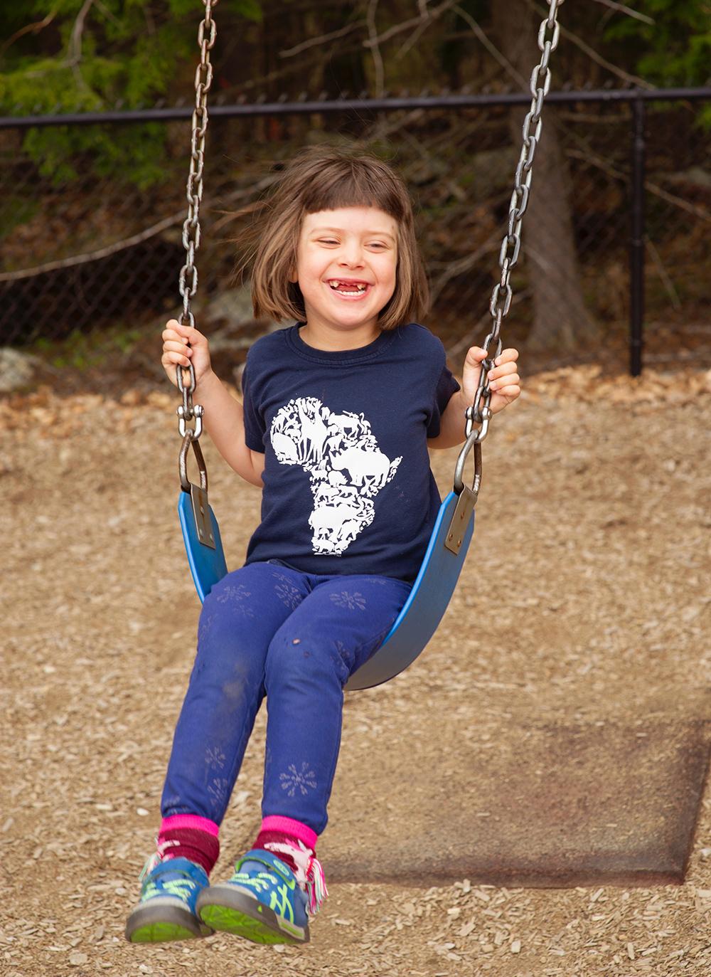 grinning girl on swing