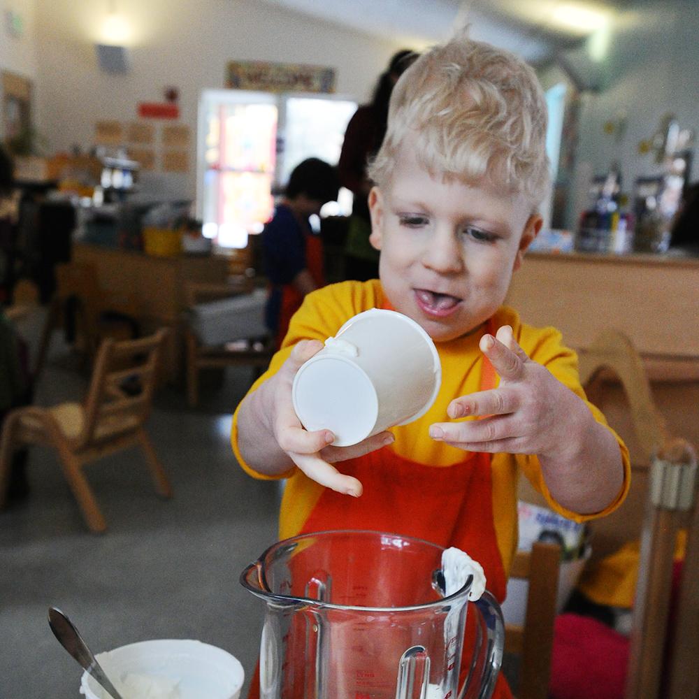 boy in apron adding yogurt to blender