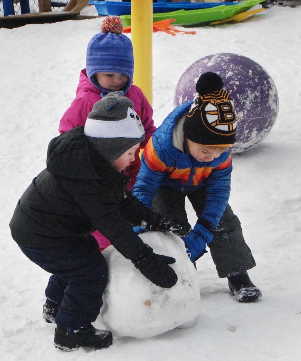 three kids making a snowman