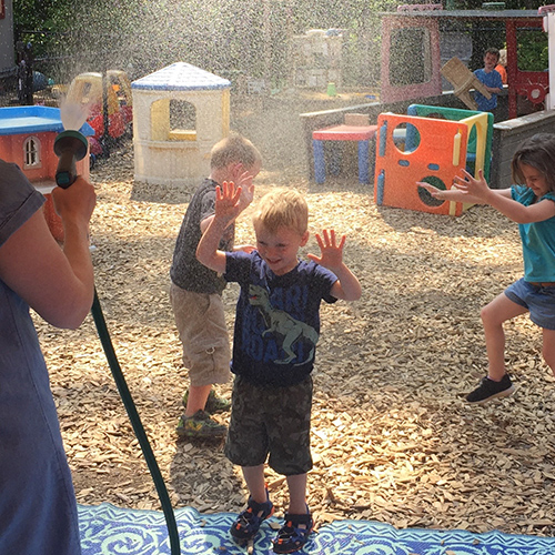 kids playing in water sprayed from hose
