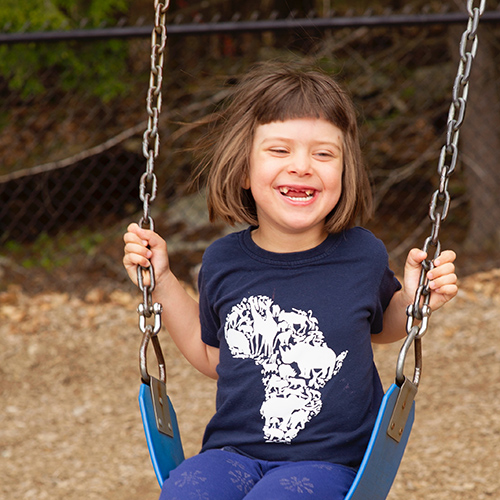 grinning girl on swing