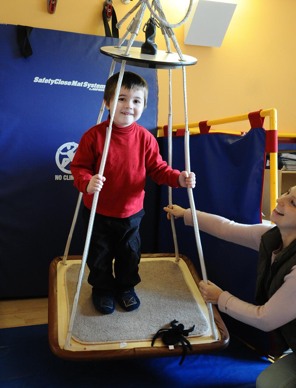 teacher encouraging a boy in a walker