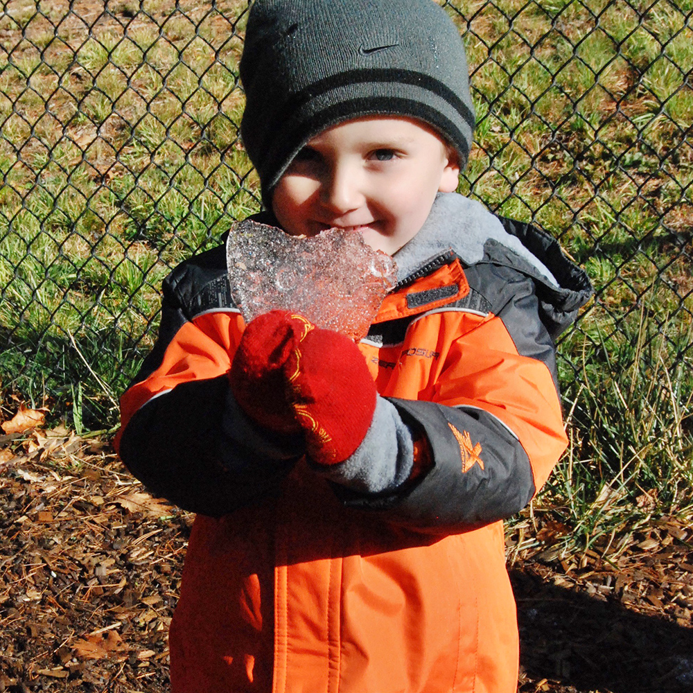smiling boy holding piece of ice in the shape of a heart