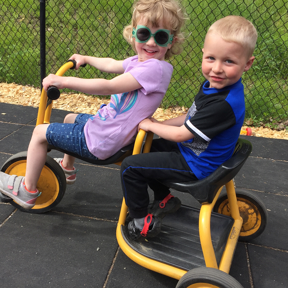 two preschoolers on a tandem trike