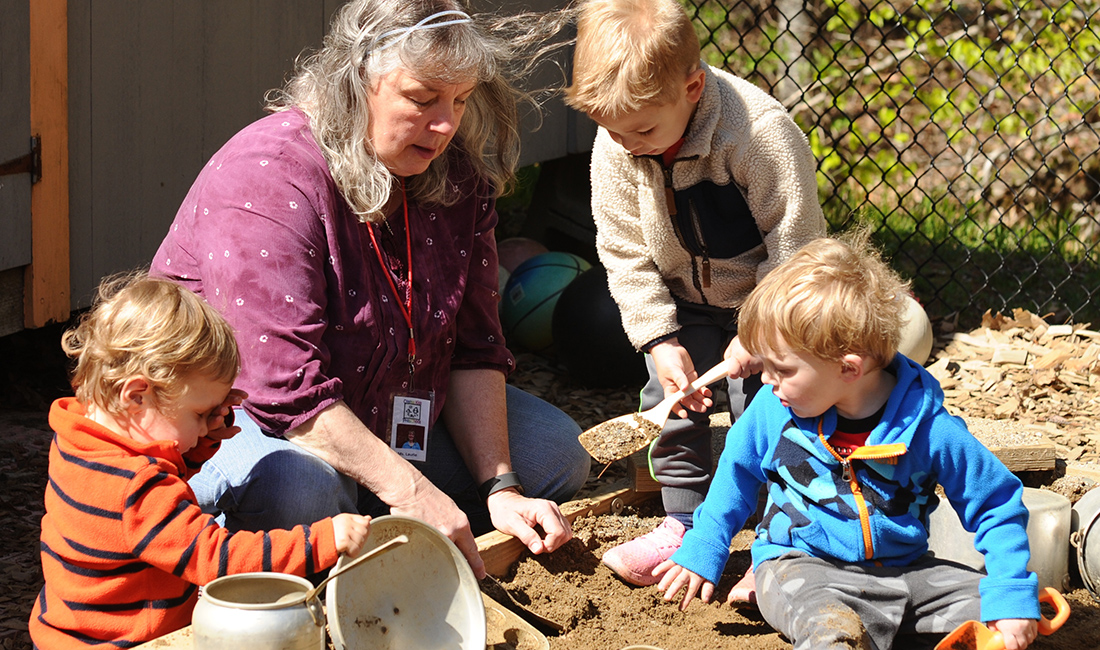 teacher and toddlers playing in sandbox